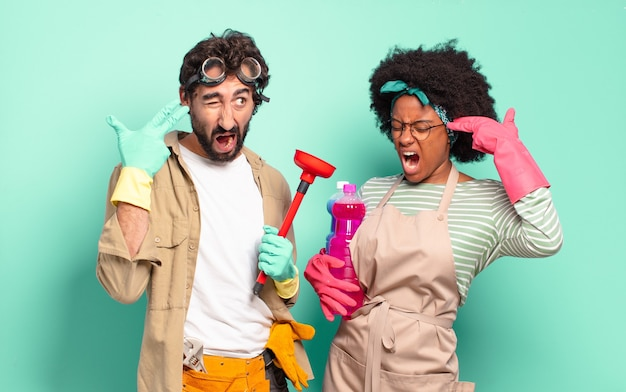 Young mixed couple holding cleaning items posing on turquoise