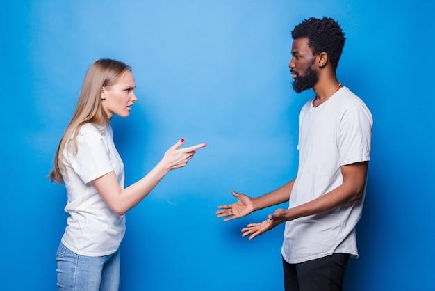 青い壁に分離された若い混合カップルの喧嘩