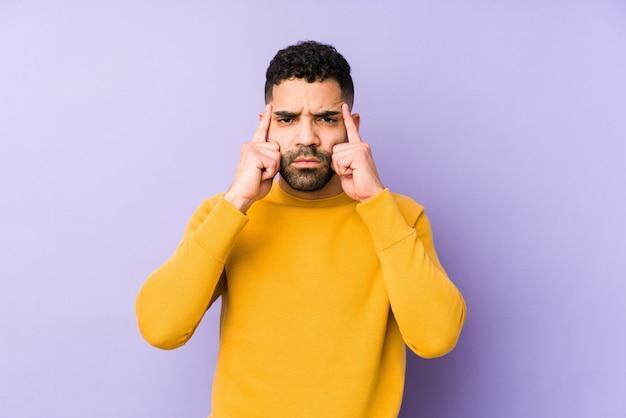 Молодой арабский мужчина смешанной расы изолировал сосредоточенный на задаче, держа указательные пальцы указывая головой.