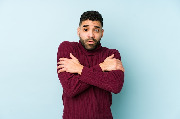 Young mixed race arabic man isolated going cold due to low temperature or a sickness.