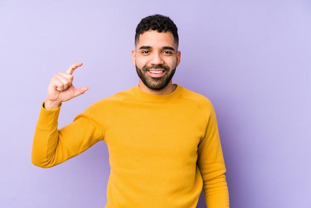 Молодой арабский мужчина смешанной расы изолировал, держа что-то немного указательными пальцами, улыбаясь и уверенно.