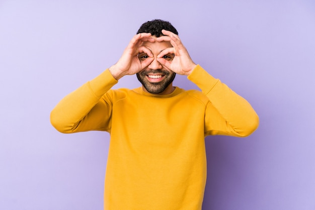Young mixed race arabic man isolated showing okay sign over eyes