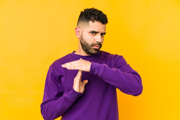 Young mixed race arabic man isolated showing a timeout gesture.