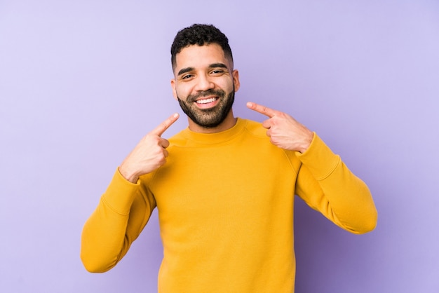 Young mixed race arabic man isolated smiles, pointing fingers at mouth.