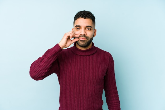Young mixed race arabic man isolated with fingers on lips keeping a secret.