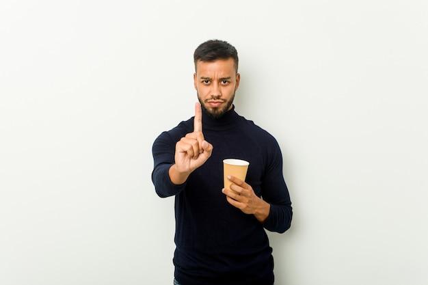 若い混血アジア人男性が指でナンバーワンを示すテイクアウトのコーヒーを保持しています。