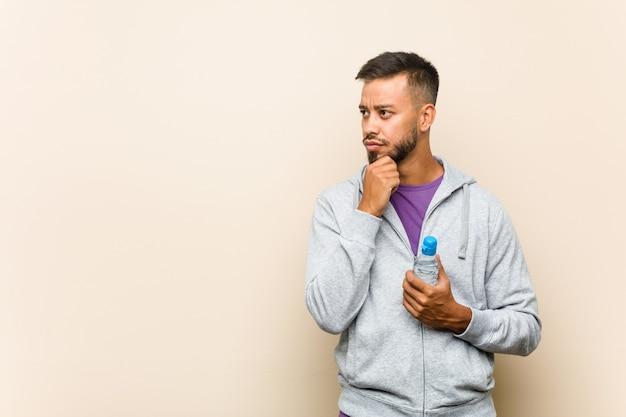 Молодой смешанной расы азиатский мужчина держит бутылку с водой