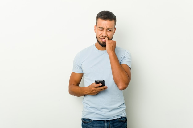 Young mixed race asian man holding a phone biting fingernails, nervous and very anxious.