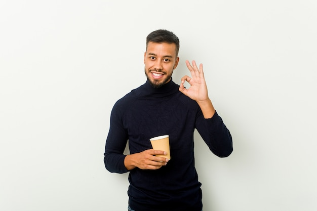 Young mixed race asian man holding a takeaway coffee cheerful and confident showing ok gesture