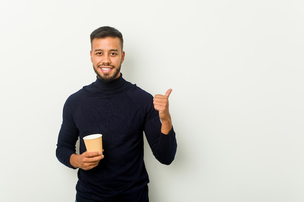 Young mixed race asian man holding a takeaway coffee smiling and raising thumb up