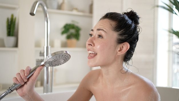 젊은 혼혈 아시아 여성이 샤워 헤드를 사용하여 욕조에서 노래하는 행복한 밀레니엄 다민족 소녀가 욕실 미용 치료 요법의 건강한 생활 방식 개념에서 매일 바디 케어를 즐깁니다.