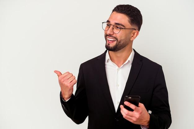 휴대 전화를 들고 젊은 혼합 된 경주 비즈니스 남자 엄지 손가락 손가락으로 멀리, 웃음과 평온한 흰색 배경 포인트에 고립.