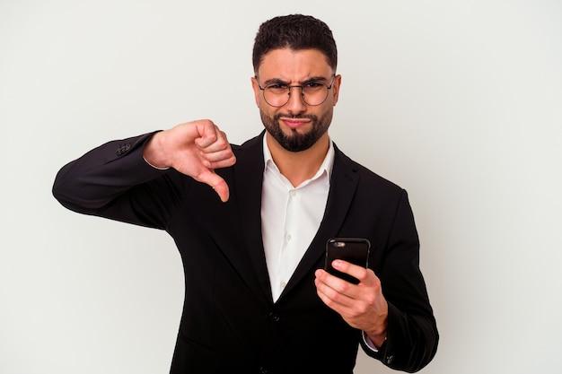 嫌いなジェスチャーを示す白い背景で隔離の携帯電話の男を保持している若い混血のビジネスマンは、親指を下に向けます。不一致の概念。