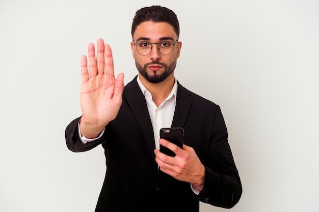 一時停止の標識を示す差し出された手で立っている白い背景に分離された携帯電話の男を保持している若い混血ビジネスマンは、あなたを防ぎます。