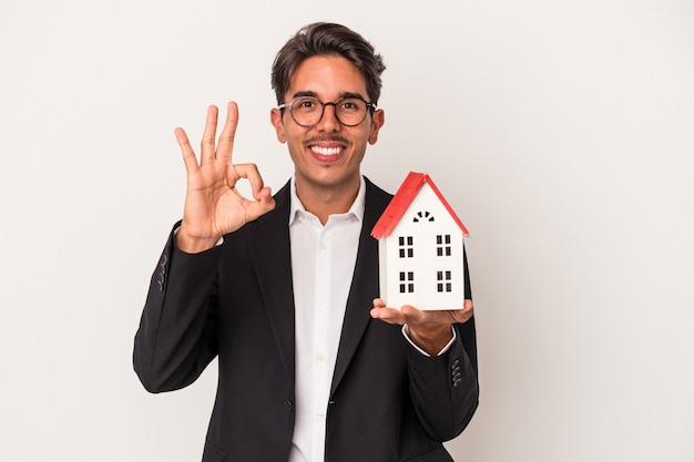 白い背景で隔離のおもちゃの家を保持している若い混血ビジネスマンは、陽気で自信を持って大丈夫なジェスチャーを示しています。