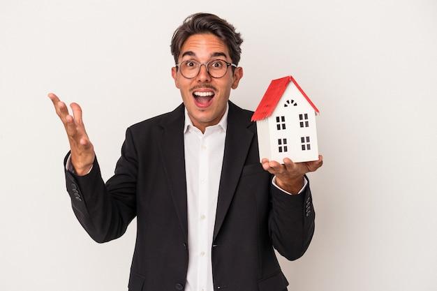 白い背景で隔離のおもちゃの家を保持している若い混血ビジネスマンは、嬉しい驚きを受け取り、興奮し、手を上げます。