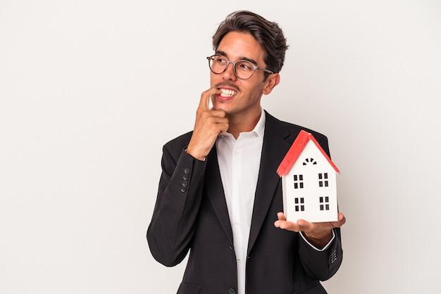 白い背景で隔離のおもちゃの家を保持している若い混血のビジネスマンは、コピースペースを見ている何かについて考えてリラックスしました。