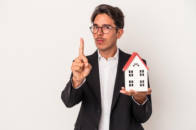 指でナンバーワンを示す白い背景で隔離のおもちゃの家を保持している若い混血ビジネスマン。