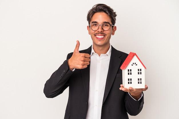 Молодой смешанной расы деловой человек держит игрушечный домик на белом фоне, улыбаясь и поднимая палец вверх