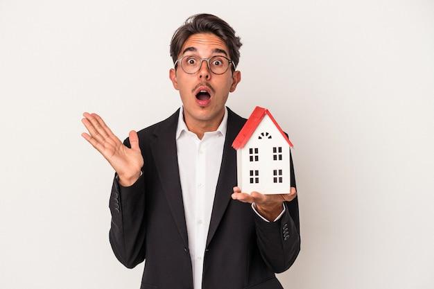 白い背景で隔離のおもちゃの家を保持している若い混血ビジネスマンは驚いてショックを受けました。
