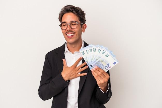 白い背景で隔離の手形を保持している若い混血ビジネスマンは、胸に手を置いて大声で笑います。