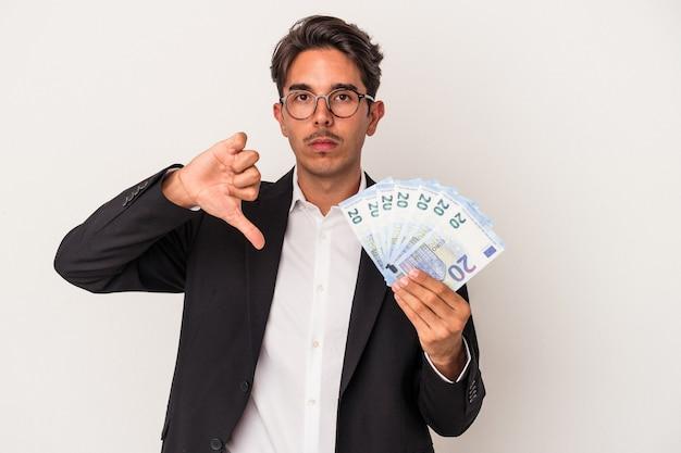 嫌いなジェスチャーを示す白い背景で隔離の請求書を保持している若い混血ビジネスマン、親指を下に。不一致の概念。