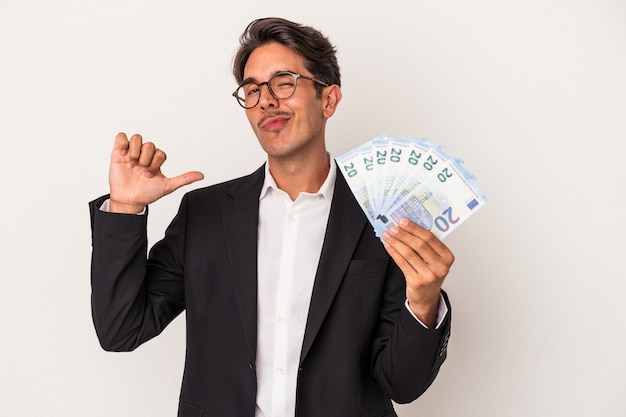 Young mixed race business man holding bills isolated on white background feels proud and self confident, example to follow.