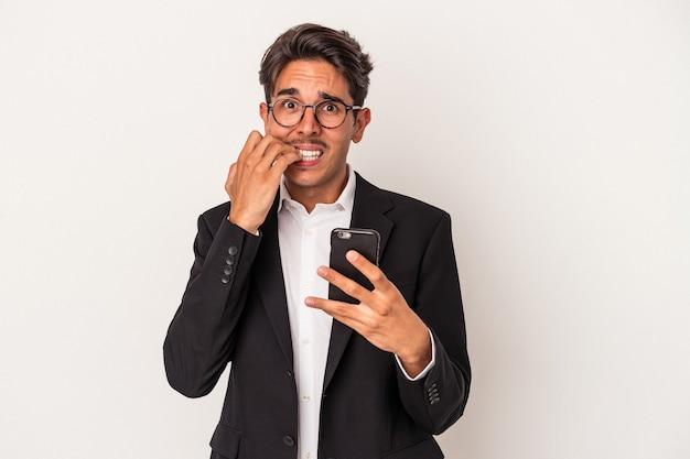 指の爪を噛んで、神経質で非常に心配している白い背景で隔離の携帯電話を保持している若い混血ビジネスマン。