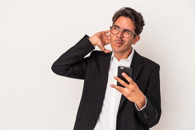 흰색 배경에 격리된 휴대전화를 들고 있는 젊은 혼혈 사업가는 머리 뒤쪽을 만지고 생각하고 선택합니다.