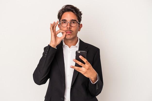 秘密を保持している唇に指で白い背景で隔離の携帯電話を保持している若い混血ビジネスマン。