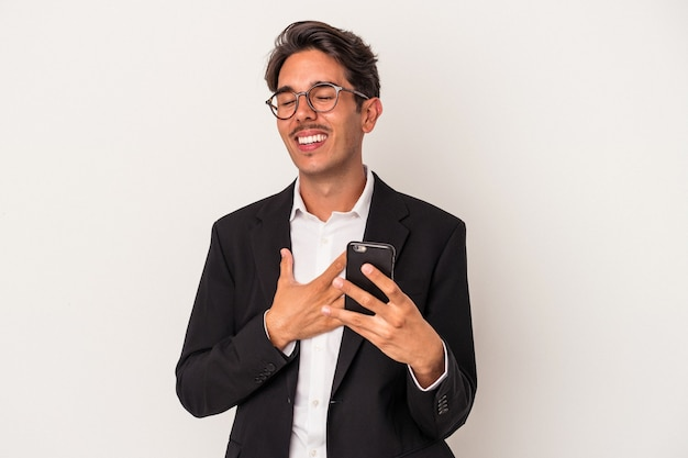 Young mixed race business man holding mobile phone isolated on white background laughs out loudly keeping hand on chest.