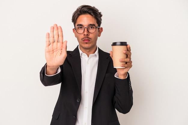 一時停止の標識を示す伸ばした手で立っている白い背景で隔離のコーヒーをテイクアウトを保持している若い混血ビジネスマンは、あなたを防ぎます。