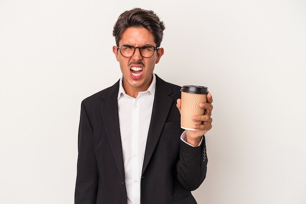 Young mixed race business man holding take away coffee  isolated on white background screaming very angry and aggressive.
