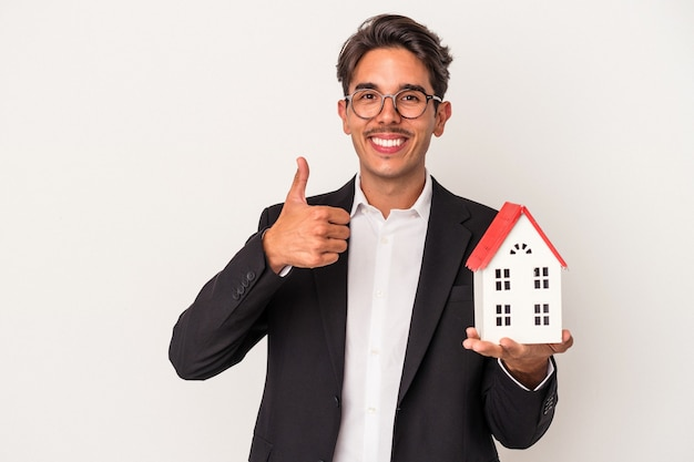 Young mixed race business man holding a toy house isolated on white background smiling and raising thumb up