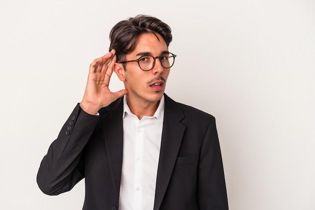 ゴシップを聴こうとしている白い背景で隔離の若い混血ビジネスマン。