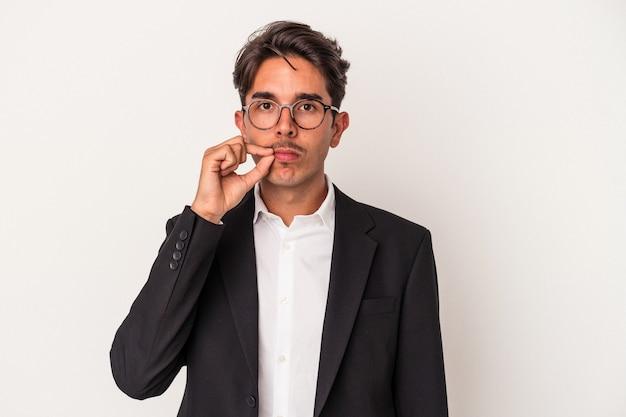 秘密を保持している唇に指で白い背景で隔離の若い混血ビジネスマン。