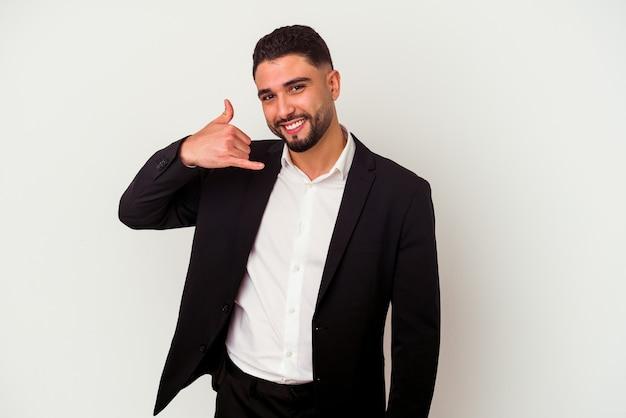 Молодой смешанной расы деловой человек, изолированные на белой стене, показывая жест мобильного телефона с пальцами.