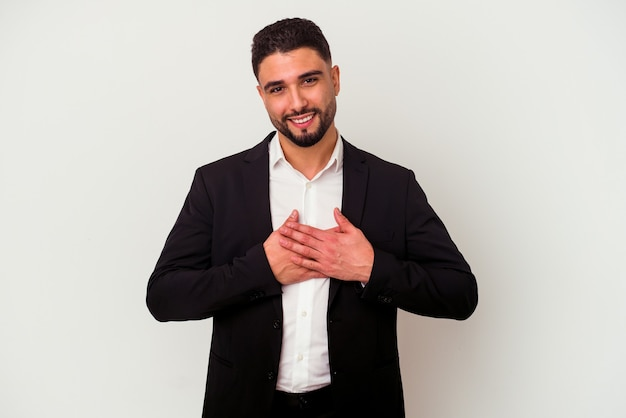 Young mixed race business man isolated on white background has friendly expression, pressing palm to chest.
