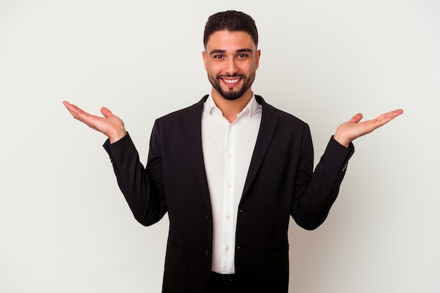Young mixed race business man isolated on white background makes scale with arms, feels happy and confident.