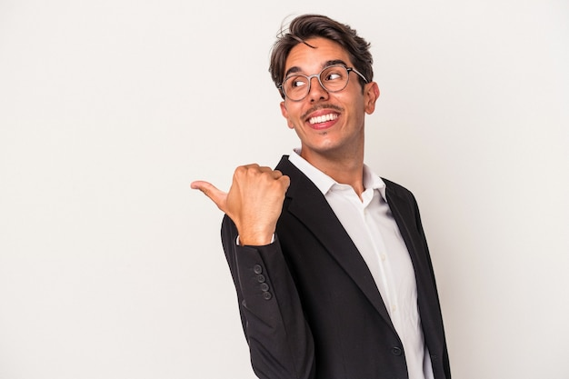 Young mixed race business man isolated on white background points with thumb finger away, laughing and carefree.