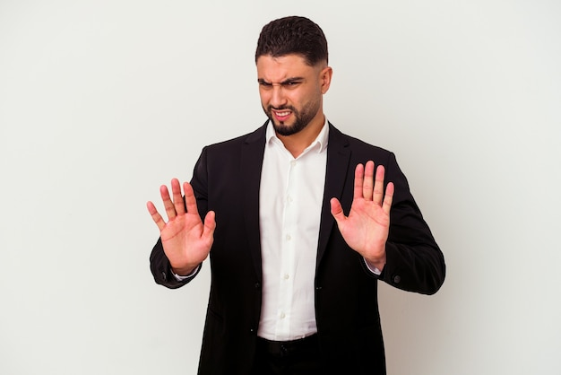 Young mixed race business man isolated on white wall rejecting someone showing a gesture of disgust.