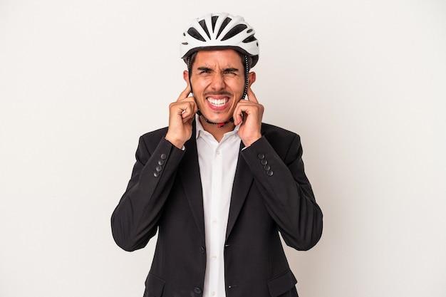 手で耳を覆う白い背景で隔離の自転車のヘルメットを身に着けている若い混血ビジネスマン。