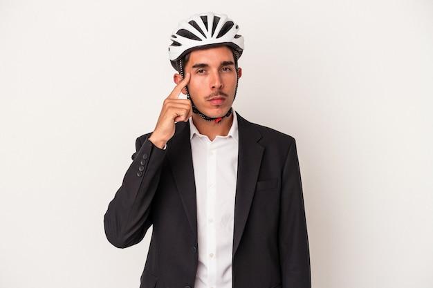 指で寺院を指して、白い背景で隔離の自転車のヘルメットを身に着けている若い混血ビジネスマンは、タスクに焦点を当てて考えています。