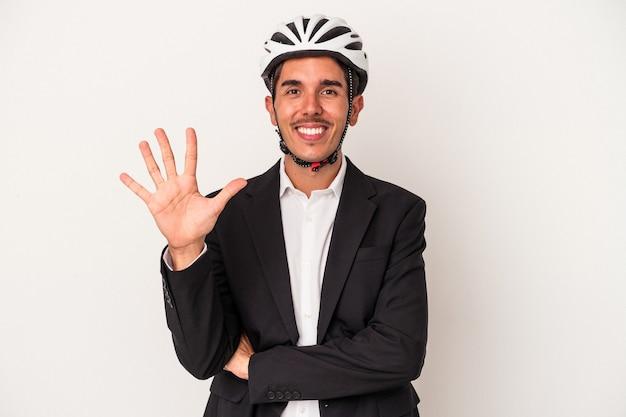 白い背景で隔離の自転車のヘルメットを身に着けている若い混血のビジネスマンは、指で5番を示す陽気な笑顔を浮かべています。