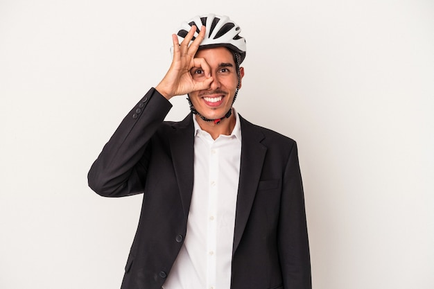 Young mixed race business man wearing a bike helmet isolated on white background excited keeping ok gesture on eye.