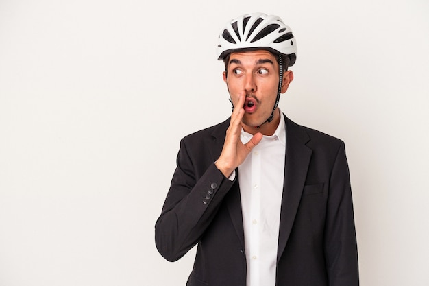 Young mixed race business man wearing a bike helmet isolated on white background is saying a secret hot braking news and looking aside
