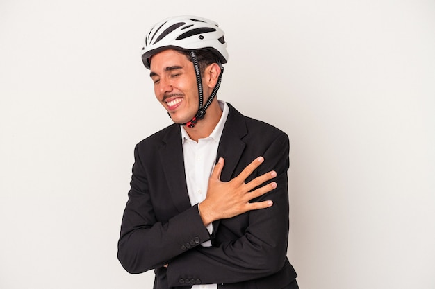Young mixed race business man wearing a bike helmet isolated on white background laughing and having fun.