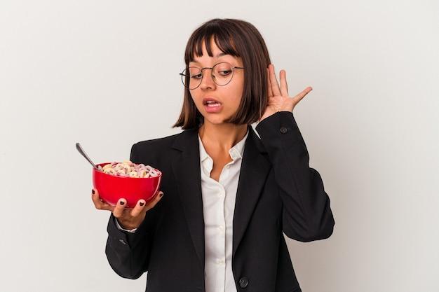 ゴシップを聴こうとしている白い背景で隔離の穀物を食べる若い混血ビジネス女性。