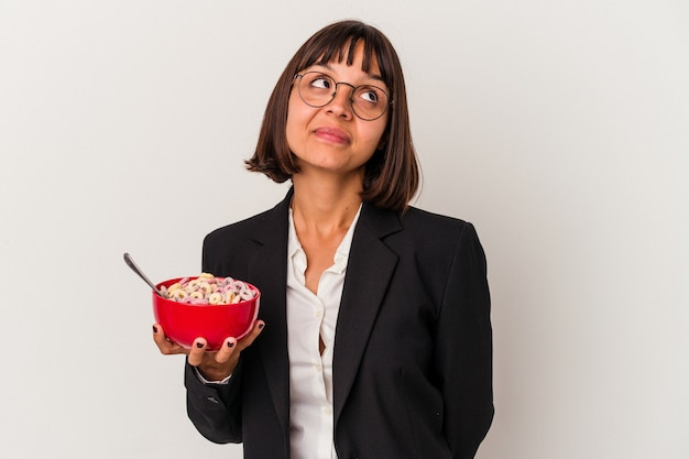 Young mixed race business woman eating cereals isolated on white background dreaming of achieving goals and purposes