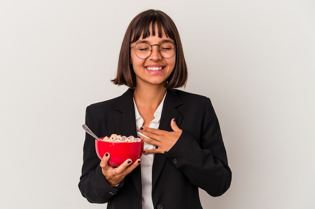 Young mixed race business woman eating cereals isolated on white background laughs out loudly keeping hand on chest.